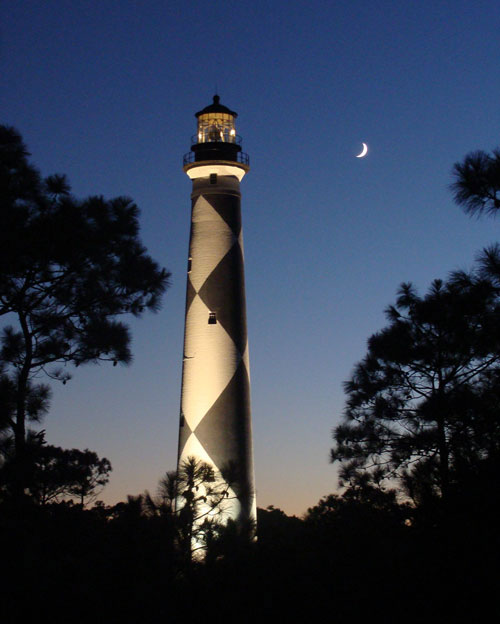 Cape lookout lighthouse at night with a quarter moon