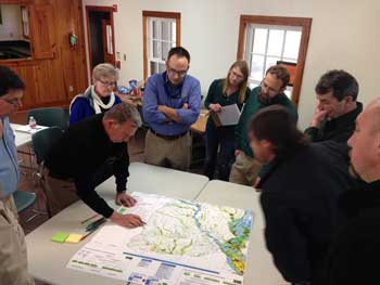 Conservationists huddle around a map with blue pens.