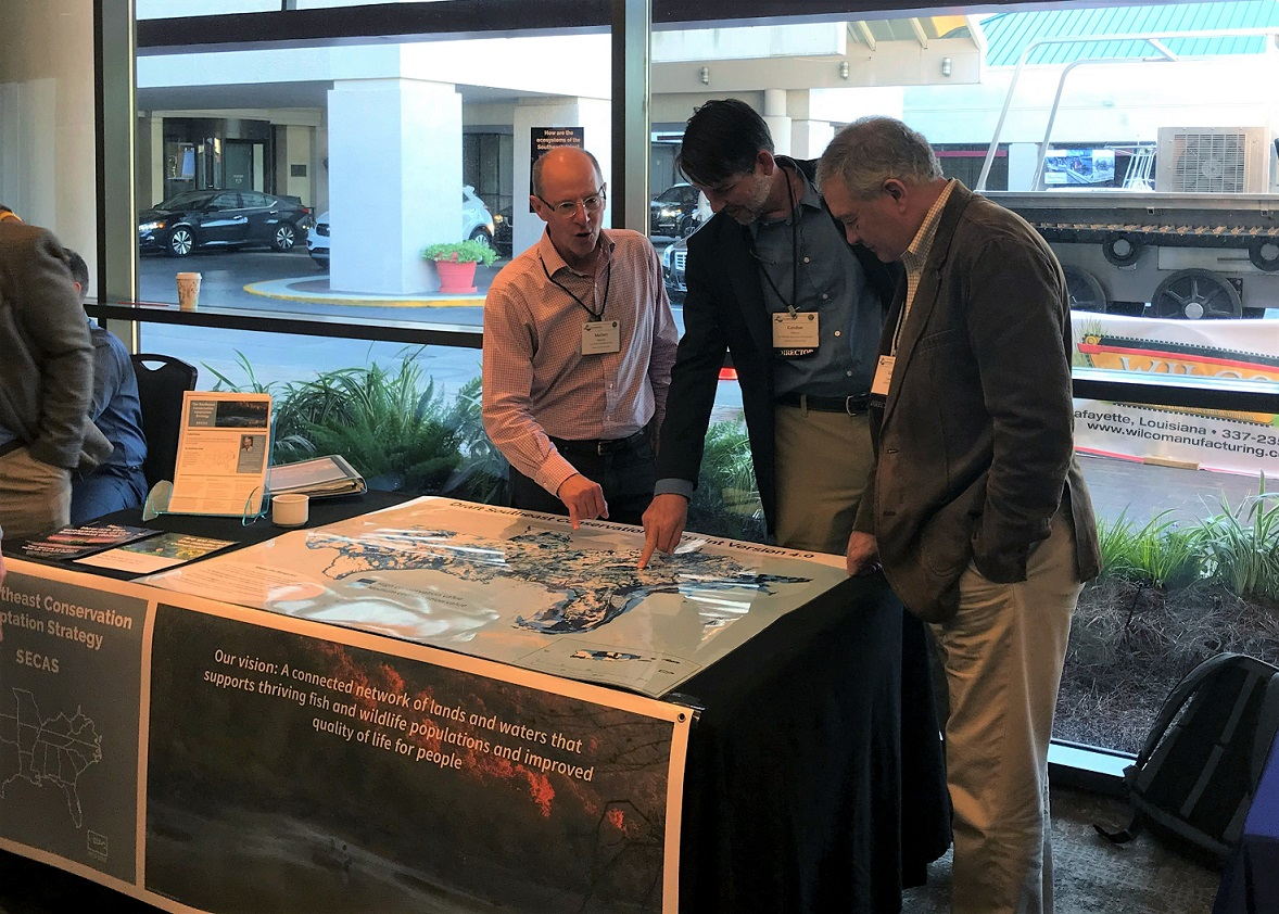 Gordon Myers and Ed Carter look at the map of Southeast Blueprint 4.0 at the SECAS exhibit booth.