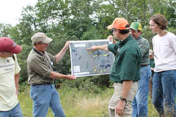 Biologists in the field gather around a map.